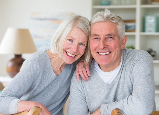 Man and woman smiling after cast metal partial denture tooth replacement