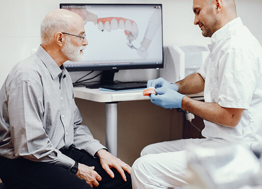 A dentist explaining a denture to an older man.