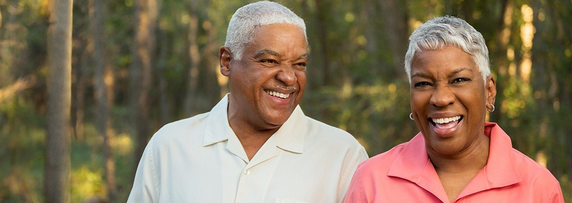 Older couple smiling together after denture tooth replacement