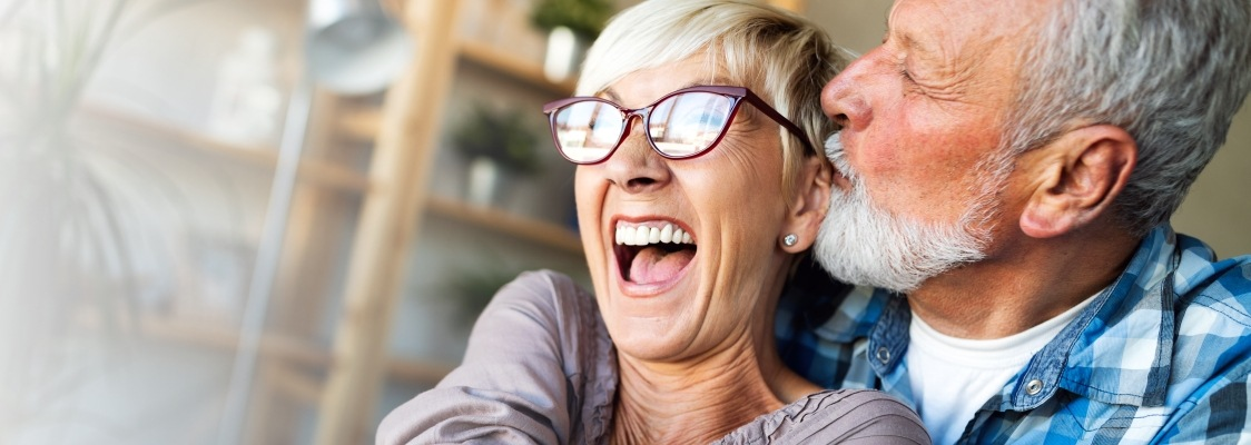 Older man and woman smiling after denture tooth replacement